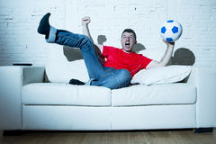 Crazy fanatic  man as football fan watching game on television wearing red team jersey celebrating goal Stock Photography