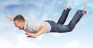 The crazy flying man in clouds Stock Images