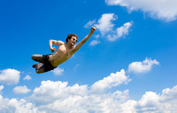 The crazy flying man in clouds. A man flying between idyllic clouds Royalty Free Stock Images