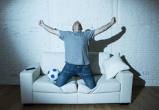 Crazy football fan watching tv soccer match alone screaming happy celebrating goal Stock Photography