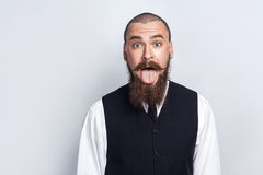 Crazy Funny face. Handsome businessman with beard and handlebar mustache looking at camera with tongue out. stock photo