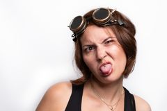 Crazy funny girl wearing steampunk glasses and piercing is making grimaces. Crazy funny girl wearing steampunk glasses making grimaces. Eyes crossed and tongue stock photos