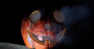 Crazy funny jack pumpkin on halloween close-up in the dark stock video