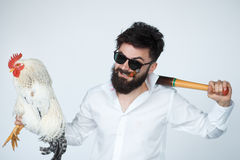 Crazy and funny mafia boss holding a cock. Italian funny mafia boss wearing white shirt and sunglasses with a cock and bat in studio Stock Image