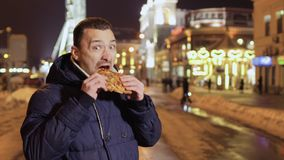 Crazy funny man eats pizza and grimaces on camera showing thumb up. Young handsome guy eats pizza at the night city background. Funny expressive guy is grimacing stock video footage