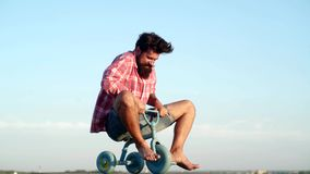 Crazy funny man rides a bike on sky background. Funny man having fun on children bicycle. Hipster with funny face. Different ages. Funny crazy man stock video