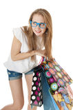 Crazy funny young girl with shopping gift bags wearing glasses. Stock Photos