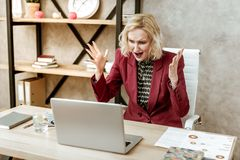 Crazy furious woman yelling on her laptop during attack of aggression. Unpleasant conversation. Crazy furious woman yelling on her laptop during attack of royalty free stock photos