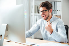 Crazy furious young businessman working and screaming Stock Photography