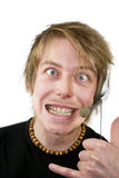 Crazy Gamer. A photograph of a male cross eyed with surf hand gesture in a crazy manner. He is wearing a headset for a games console suggesting Internet gaming Stock Photos