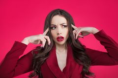 Crazy girl on pink background. Young beautiful woman with bright makeup. The brunette grabbed her head. Copy space stock image