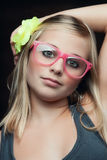 Crazy girl posing. A young girl with pink glasses an a yellow flower in the hair posing with her arm over her head Royalty Free Stock Image