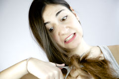 Crazy girl starting to cut her long hair for desperation of betrayal. Woman being betrayed decides to cut her long hair Stock Photo