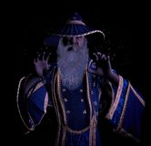 Crazy Grumpy Old Wizard Casting Magic Spell. A wizard with his both hands grasping towards the subject in front Royalty Free Stock Photography