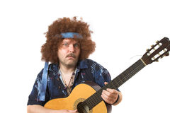 Crazy guitar player. Old hippie putting on a face while playing his guitar royalty free stock photo