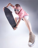Crazy guy jumping with a skateboard making funny faces Stock Photos