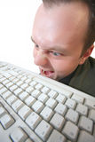 Crazy hacker. Eats keyboard because he is hungry or mad (isolated on white Royalty Free Stock Image