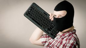 Man wearing balaclava holding keyboard Royalty Free Stock Images
