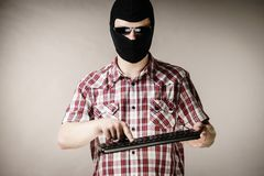 Man wearing balaclava holding keyboard Royalty Free Stock Photos