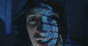 Close up of Crazy hacker programmer in hood with binary code reflection on his face in dark room at night. Portrait of. Crazy hacker programmer in hood with stock footage