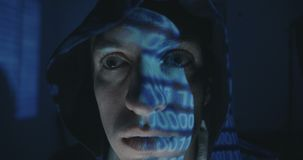 Close up of Crazy hacker programmer in hood with binary code reflection on his face in dark room at night. Portrait of. Crazy hacker programmer in hood with stock video