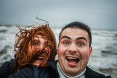 Crazy happy couple by the sea in storm weather Royalty Free Stock Images