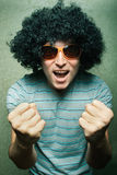 Crazy happy dude in afro wig. Crazy young guy in afro curly wig with eyeglasses stock photos