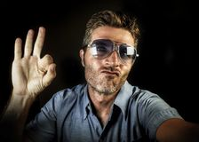 Crazy happy and funny guy with sunglasses and modern hipster look taking selfie self portrait picture with mobile phone camera smi. Ling cool and giving ok sign royalty free stock images
