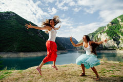 Crazy happy jump in mountains. Of two long hair girls with exciting landscape view of Montenegro stock photography