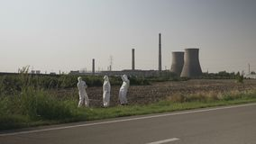 Crazy hazmat team of workers dancing near a nuclear power plant funny concept of ecology -. Crazy hazmat team of workers dancing near a nuclear power plant funny stock footage