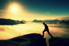 Crazy hiker in black is jumping between the rocky peaks. Wonderful daybreak in rocky mountains, heavy mist in deep valley. Miracle Royalty Free Stock Image
