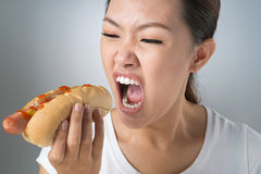 Crazy for hot-dog. Asian girl devouring greedily a hot-dog royalty free stock photography