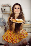 Crazy housewife on kitchen smiling eating Royalty Free Stock Photography