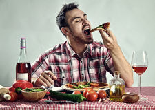 Crazy hungry man eating pizza stock photography
