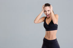Crazy hysterical shouting fitness girl in black top and leggings. Isolated over grey background Royalty Free Stock Image