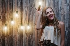 Crazy idea lamp woman. Beautiful young girl woman lady holding in hand a light bulb, she had a brilliant idea. Illumination of consciousness smart idea Stock Image