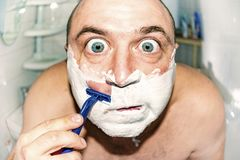 Crazy and insane man shaves in the bathroom, wide-angle photo.  royalty free stock images