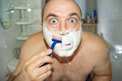 Crazy and insane man shaves in the bathroom, wide-angle photo.  stock photo