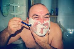Crazy and insane man shaves in the bathroom, wide-angle photo.  royalty free stock photo
