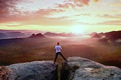 Crazy jumping hiker in black celebrate triumph between two rocky peaks above mist.. Wonderful  autumn daybreak. Royalty Free Stock Photography