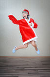 Crazy jumping Santa Claus. Crazy lady jumping indoors in Santa costume stock photography
