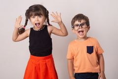 Crazy kids! Bright kids. Happy boy and girl isolated on grey. Fun children background. stock photos