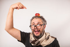 Crazy looking grumpy old man with grey beard nerd big glasses. Old man with beard and big nerd glasses with apple on head is surprised and showing with fingers Royalty Free Stock Photos