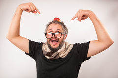 Crazy looking grumpy old man with grey beard nerd big glasses. Old man with beard and big nerd glasses with apple on head is surprised and showing with fingers Stock Images