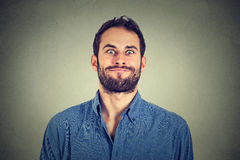 Crazy looking man making funny faces. On gray wall background Stock Photo
