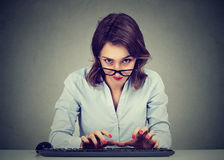 Crazy looking nerdy young woman typing on the keyboard wondering what to reply. Crazy looking nerdy woman typing on the keyboard wondering what to reply Royalty Free Stock Photos