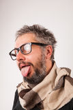 Crazy looking old man with grey beard with nerd big glasses. Crazy looking old man with grey beard and big nerd glasses show tongue Royalty Free Stock Photos