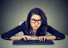 Crazy looking woman typing on the keyboard plotting a revenge Stock Image
