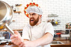 Crazy mad chef cook threatening with frying pan. On the kitchen Royalty Free Stock Images