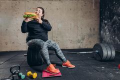 Crazy mad overweight girl tasting fast food during bodybuilding workout royalty free stock image